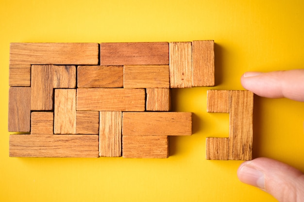 女性の手がタスクを終えるための木製のブロックを置く