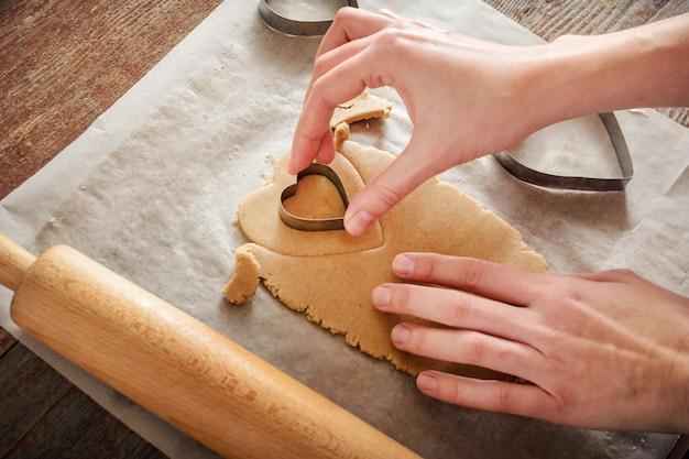 女性は木製のテーブルの上の金属の形をしたハートの形のジンジャークッキーを刻みます