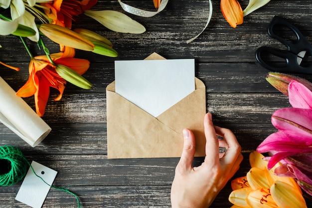 暗い背景の木のユリの花とモックアップホワイトグリーティングカードとクラフト封筒