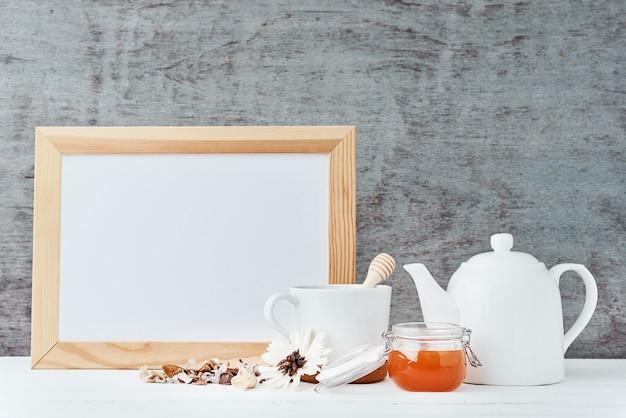 空のホワイトペーパー、ティーポット、カップ、ガラスの瓶に蜂蜜と台所用品の背景