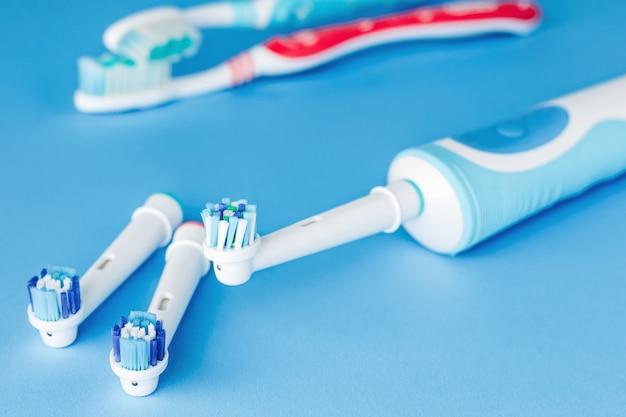 Электрическая и ручная зубная щетка на синем фоне