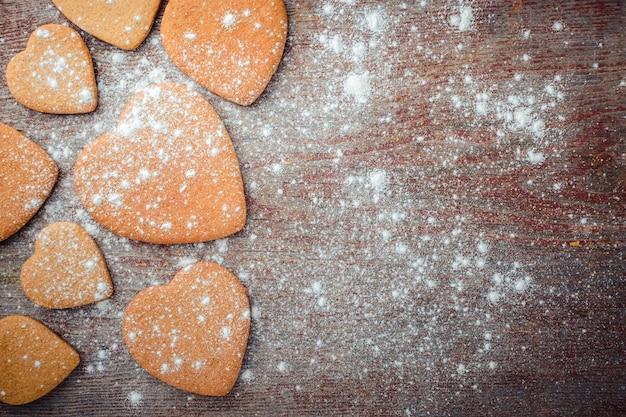 グレーの木製テーブルの上のジンジャービスケットのパターンは小麦粉を振りかけた。上面図