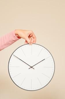 女性の手が白い背景の上の壁時計を保持します。