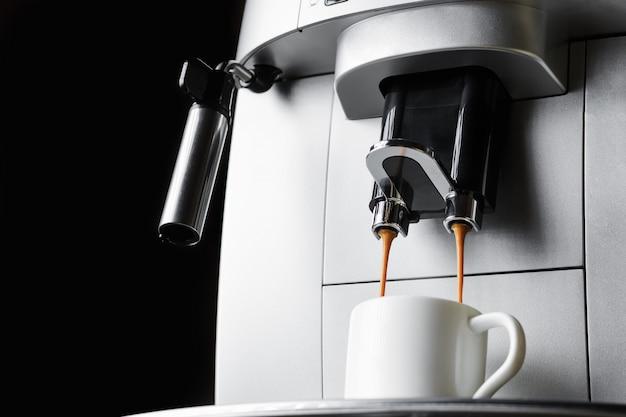 Современная кофемашина варит кофе эспрессо в белой чашке