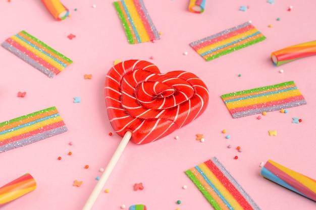 ハートとピンクの背景にカラフルなお菓子の形をした赤いロリポップ