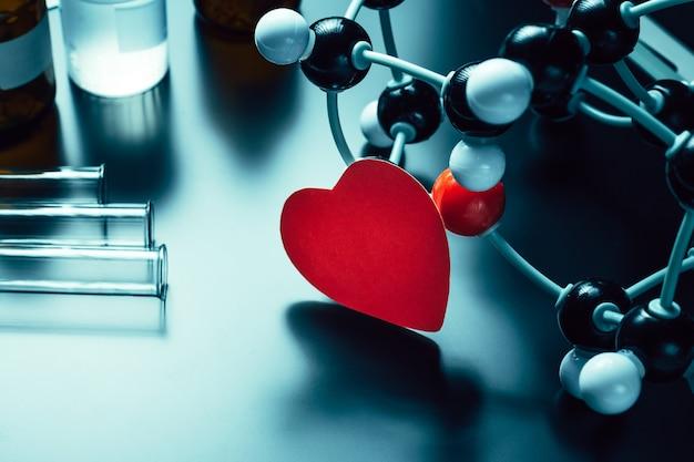 黒い背景に赤い紙の心と分子構造モデル。愛化学の概念