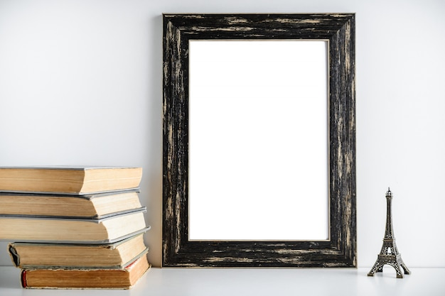 Черная рамка макета. игрушка башня и старые книги возле рамки на белом фоне.