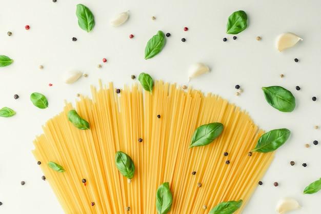 パスタ、バジル、ニンニク、コショウ、白い背景の上のコンセプト食品。