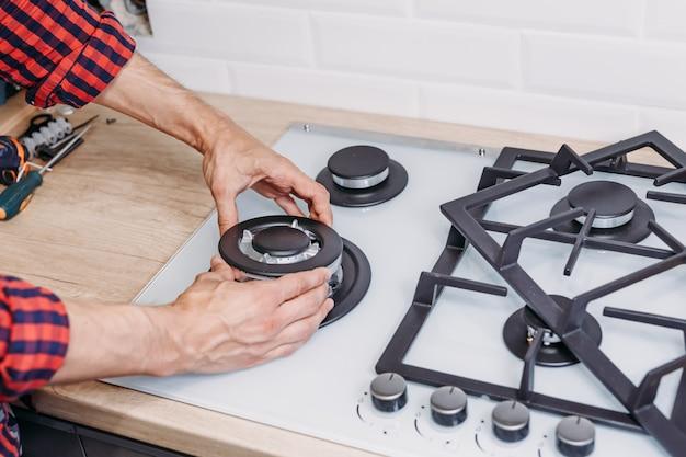 男の手のクローズアップキッチンでバーナーオンガスコンロをインストールします。ガスコントロールパネルの修理