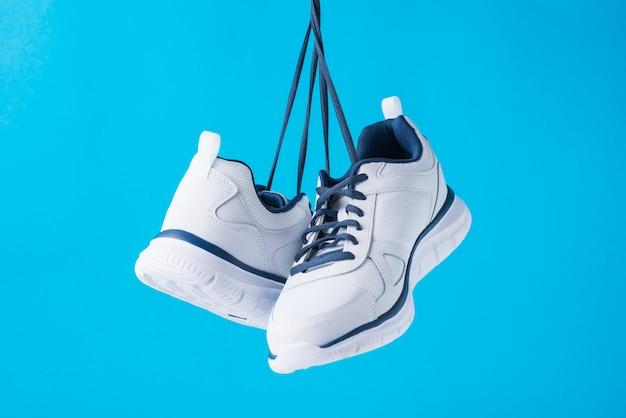 青色の背景にファッション男性スポーツシューズ。フィットネスのためのスタイリッシュな男スニーカーをクローズアップ