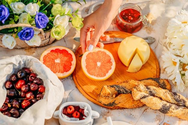 公園で夕暮れ時のピクニック。フルーツ、チーズ、テーブルクロスの上のクロワッサン