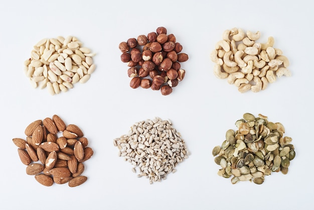 Арахис, кешью, фундук, миндаль, тыквенные семечки и семена подсолнечника на белом фоне изолированные