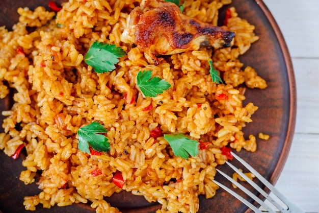 Жареный рис с овощами и курицей на деревянном столе