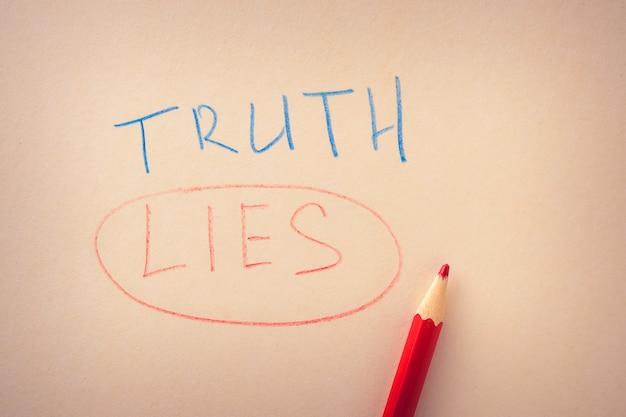 紙の上に色鉛筆で書かれた真実の言葉と下線が引かれた嘘