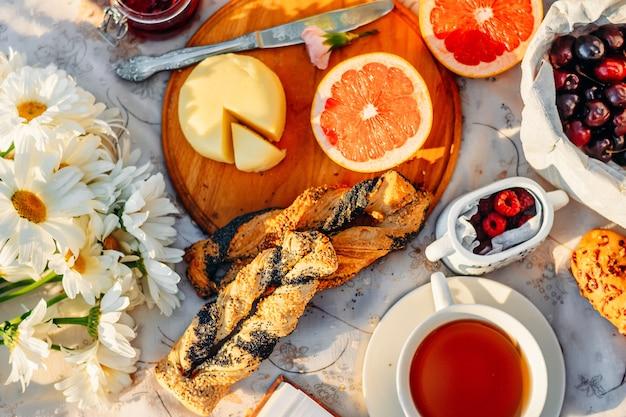 果物、クロワッサン、紅茶、夏の日差しの中でテーブルクロスの上の花。ピクニックのコンセプト
