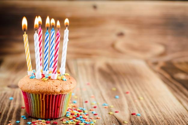 木製の背景に火をつけたキャンドルでお祝いケーキ