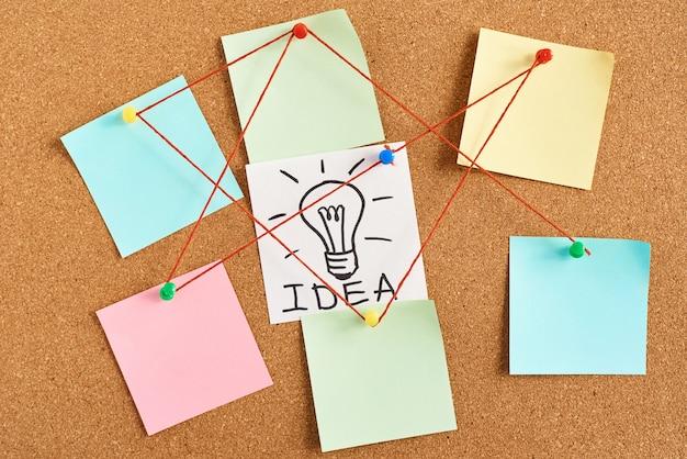 Окрашенная лампочка с идеей слова и цветными пустыми нотами