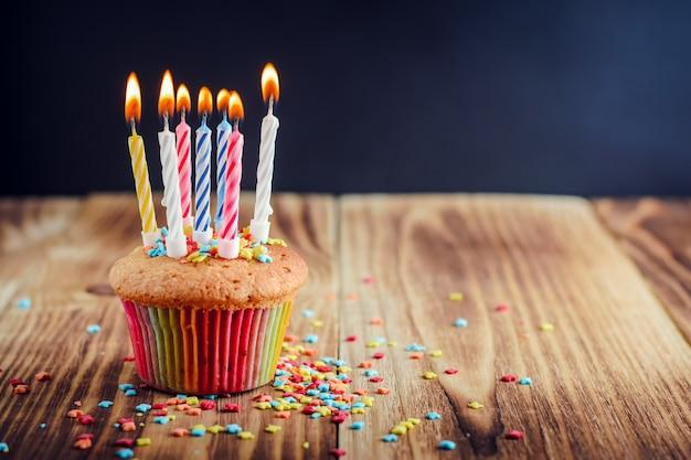 火をつけたお祝いキャンドルで飾られたカップケーキ