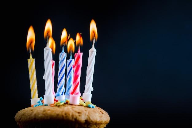 黒の背景にお祝いキャンドルを燃焼とケーキ