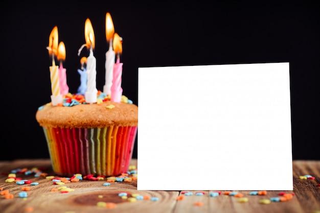 空の白い分離フレームと暗い背景にキャンドルで飾られたケーキ