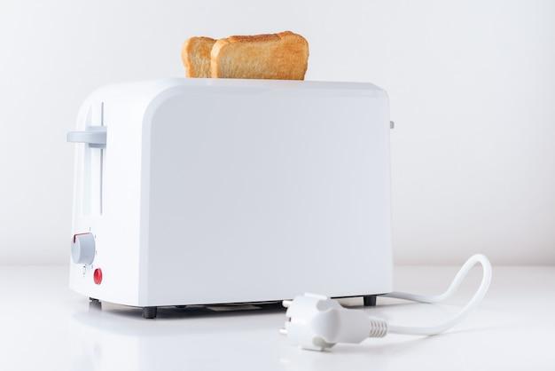 Тостер с жареным тостовым хлебом на белом