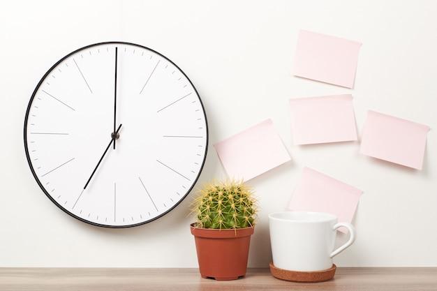 掛け時計、ピンクのステッカー、サボテンと白のカップ。ワークスペースモックアップ