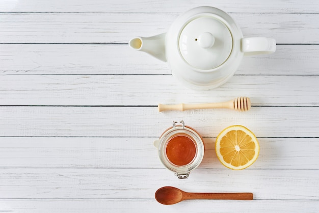 Мед в стеклянной банке, чайник и лимон на белом, вид сверху с копией пространства
