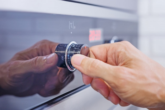 男の手が電気オーブンで調理モードを設定します。オーブンのコントロールパネルの男性の指を押すボタン、クローズアップ