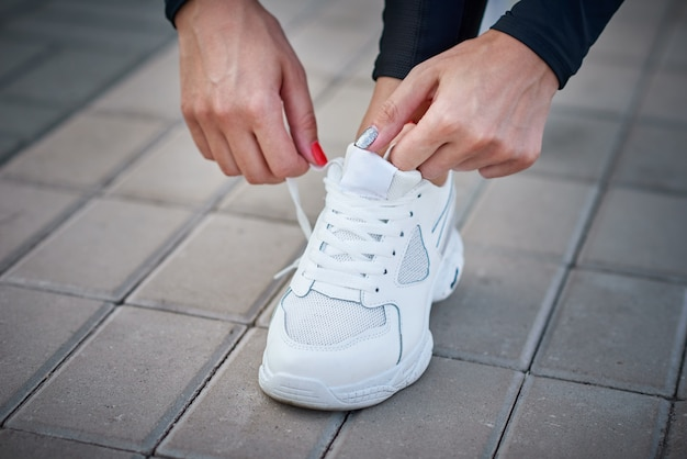 女性は走る準備ができています。スポーツスニーカーの靴ひもを結ぶ女性の手