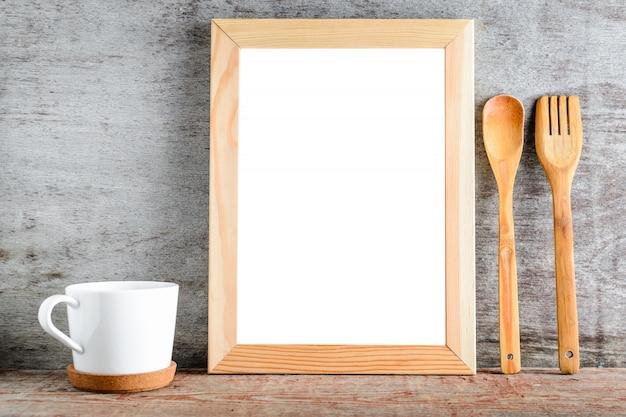 孤立した白い背景と木製のテーブルの上の台所用品を持つ空の木製フレーム。