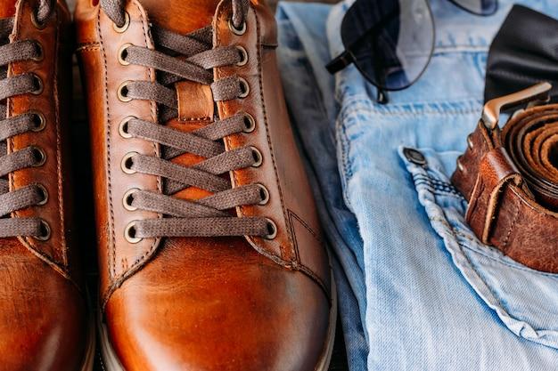 Крупным планом коричневые кожаные мужские сапоги, ремень, солнцезащитные очки и синие джинсы