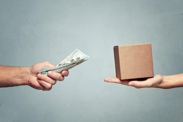 Мужчина платит деньги за подарочную коробку женщине