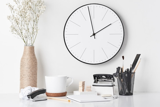 Канцелярские товары и настенные часы на белом