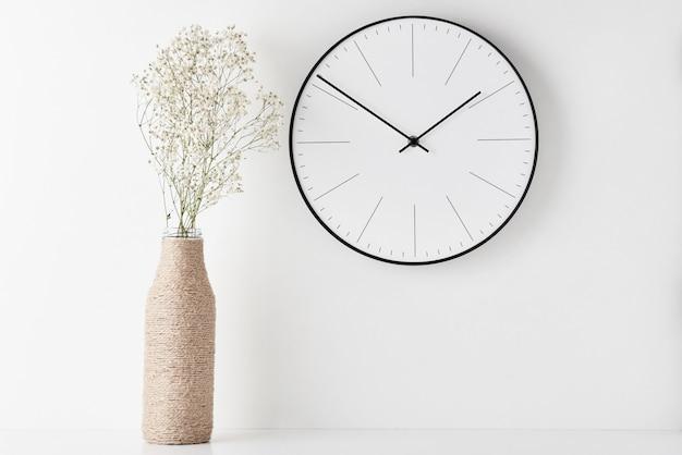 壁掛け時計付きホームオフィスの最小限のワークスペースデスク