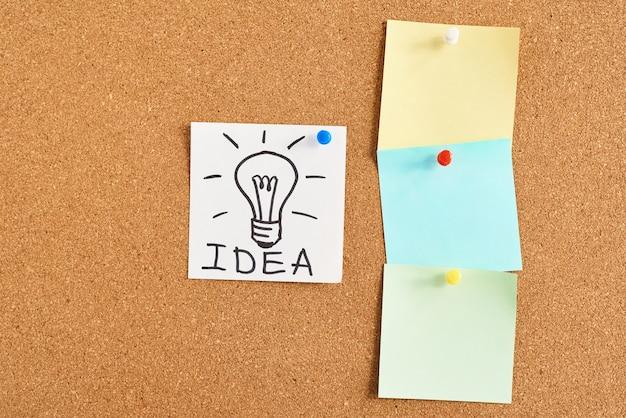 Окрашенная лампочка с идеей слова и цветные пустые заметки на пробковой доске