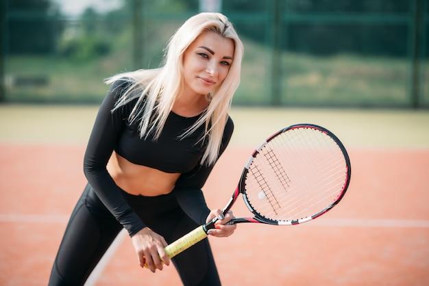裁判所でテニスをしている若い美しい女性。健康的なスポーツライフスタイル