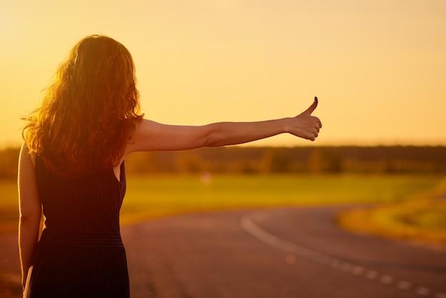 Туристическая женщина ждет автомобиль на дороге, открытый в закат