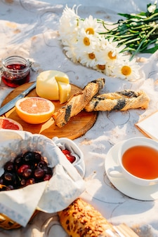 果物、クロワッサン、ジャム、紅茶、夏の日差しの中でテーブルクロスの上の花。ピクニックのコンセプト