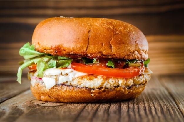 チキンチーズと木製の背景のソースのハンバーガー。