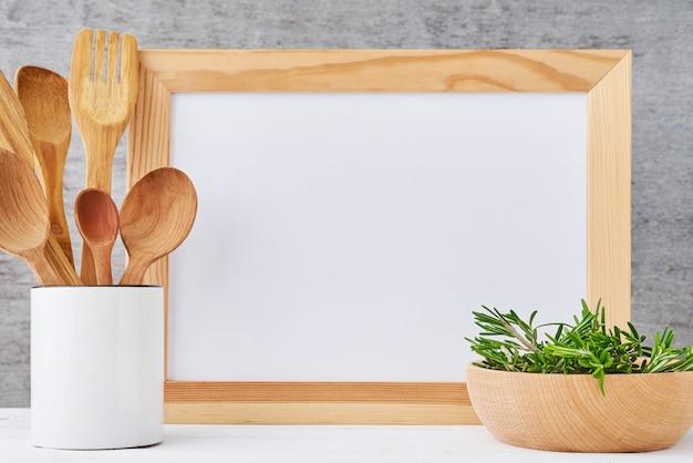空のホワイトペーパーとカップの木製カトラリーキッチン用品の背景