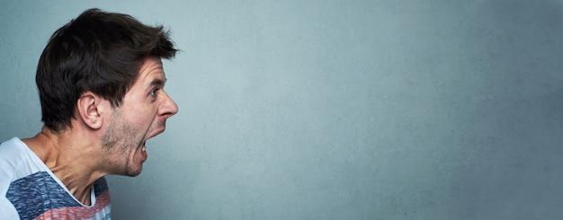 灰色の壁、コピースペースを持つ長いバナーで叫ぶ男の肖像。悲鳴を上げる顔