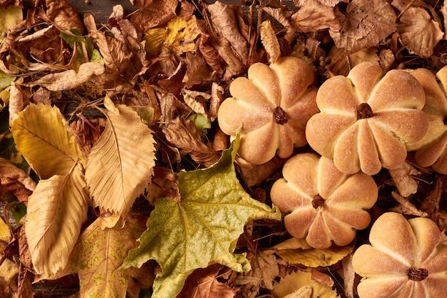 Домашнее печенье в форме тыквы в осенние листья. хэллоуин печенье ручной работы на столе, крупным планом