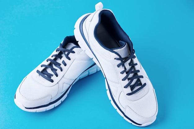 青色の背景に男性の白いスニーカーのペア。スポーツ靴のクローズアップ