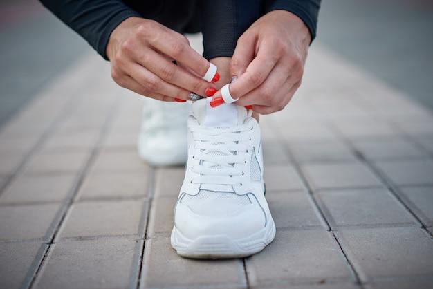 女性は実行の準備をします。スポーツスニーカーの靴ひもを結ぶ女性の手