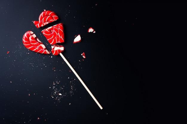 Сломанный леденец в форме сердца на темном с копией пространства