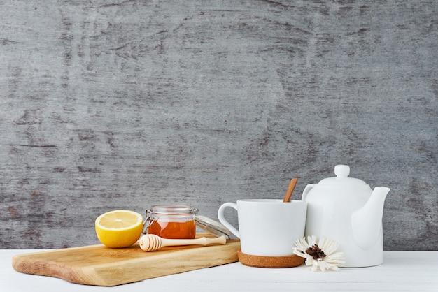 Керамический чайник, белая чашка, мёд в стеклянной банке и лимон на деревянном