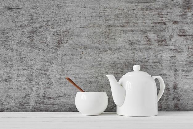 Чайник и сахарница на сером
