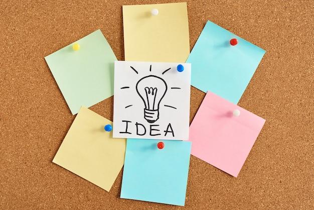 Окрашенная лампа лампочка с идеей слова и цветные пустые заметки на пробковой доске