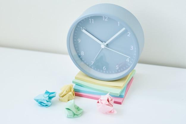 灰色の丸い目覚まし時計とカラフルな付箋