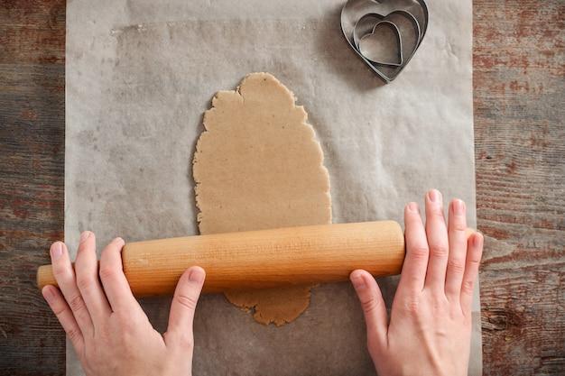 女性は麺棒で生地をロールします